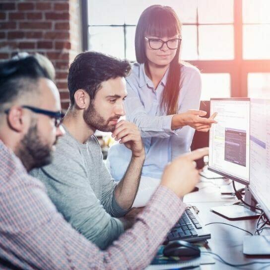 3 people working together designing website